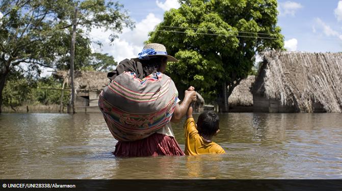 Madre ayudando a niño a cruzar inundación